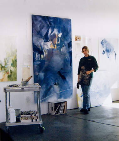 Peggy Gyulai standing in her studio next to her painting Philadelphia Orchestra