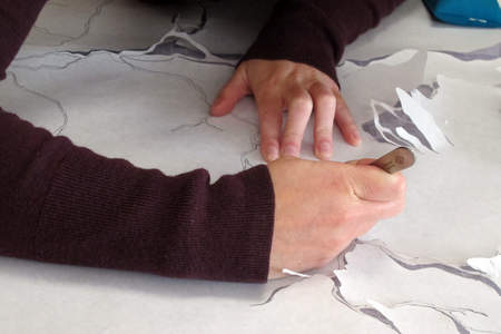 Creating the mockup, a conservator traces the web-like form onto paper