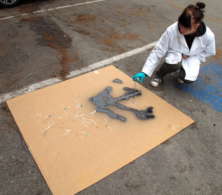 A conservator spray paints the outline of the piece through a stensil