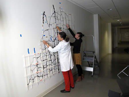 Conservators hang the mock-up on the wall to test out installation options