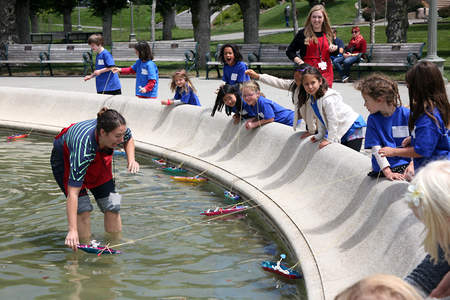 A teaching artist wades into a fountain to help young artist's boats stay afloat