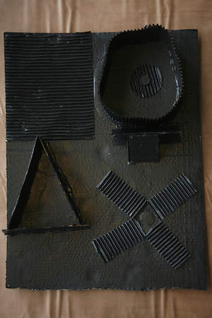 A black-on-black relief sculpture in the style of Louise Nevelson