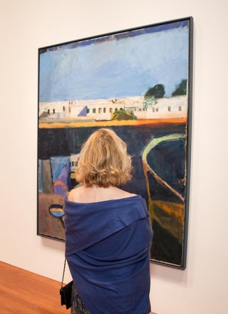 A woman in a blue shall looks at a large painting depicting an abstracted cityscape