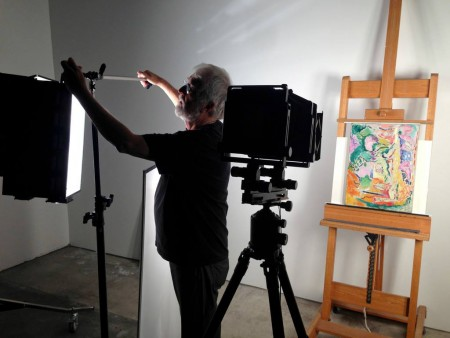 A photographer adjusts lights to better see a Matisse painting on an easel