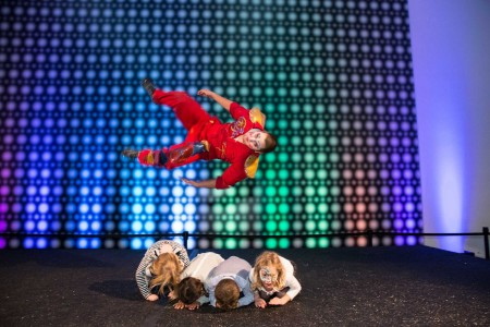 An acrobat is pictured in midair as he flips horizontally over four crouching children