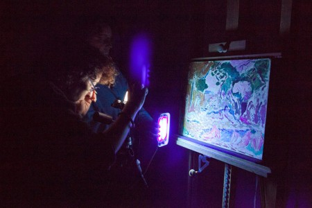 A blue/black ultraviolet light is pointed at the painting in a darkened room