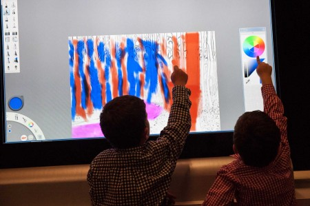 "Two children reaching up are silouhetted against the colorful digital backdrop of a huge ""iPad"""