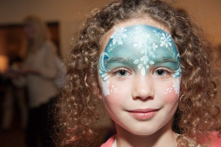 A little girl with curly hair shows off a shimmering blue facepainted mask that covers the entire top half of her face