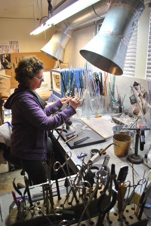 A woman wearing purple in a studio with glass-blowing tools