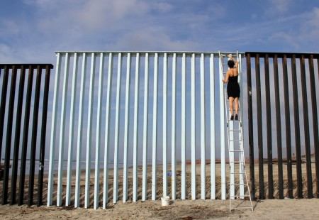 A woman dressed in black climbing over a metal fence.