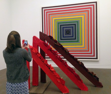 A visitor uses an iPhone to take a picture of a Frank Stella painting in our permanent collection