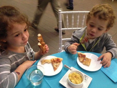Two young kids, a boy and a girl, eat pizza and mac & cheese on a turquoise table cloth