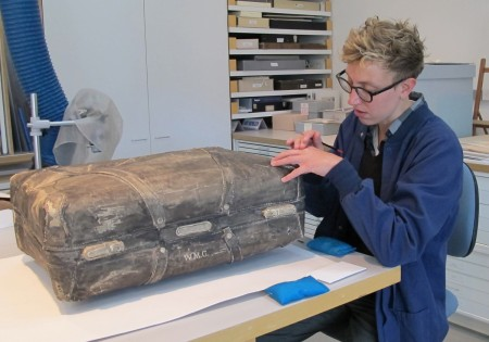 Conservation intern Laura Neufeld works on Pier Gustafson's paper suitcase
