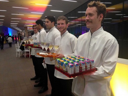 Waiters in white coats lined up offering trays laden with juice boxes