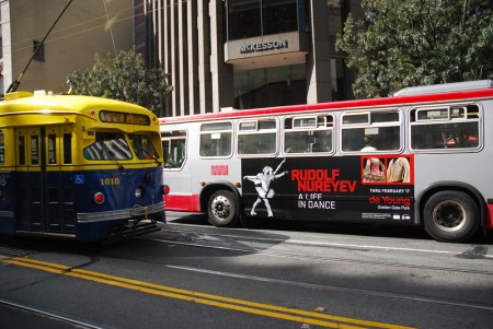A San Francisco city bus with a poster featuring the ballet dancer Rudolf Nureyev