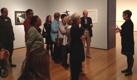 A woman leads a tour group through museum galleries