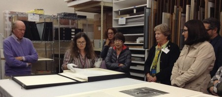 A group stands around a table looking at artworks on paper