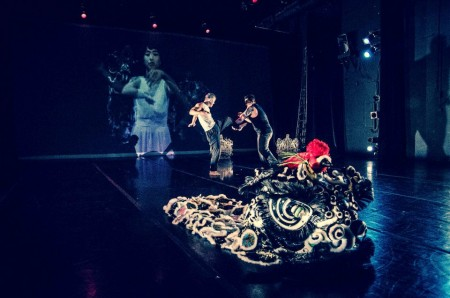 Dancers wrestle with a Chinese dragon with projected images on a scrim
