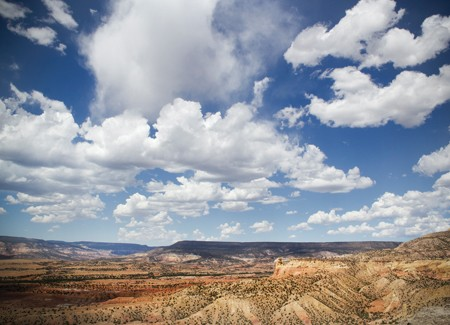 A huge blue sky with puffy white clouds looms large over a desert landscape