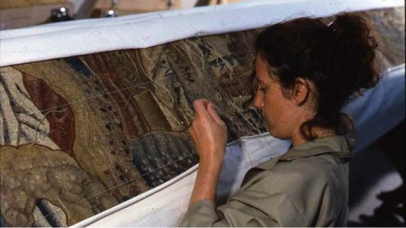 A textile conservator stiches the supportive backing onto the tapestry's reverse