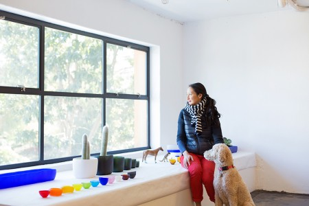 Designer Tina Frey in her light-filled studio with colorful resin blows lined up before her.