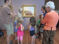 Family and group looking at painting