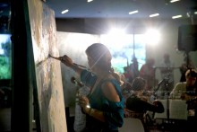 Peggy Gyulai painting to live music on a Friday Night at the de Young