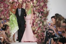 A man in a black suit stands on a runway with a female on each side