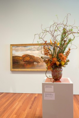 John George Brown, On the Hudson, 1867. Oil on canvas. FAMSF, gift of Mr. and Mrs. John D. Rockefeller 3rd, 1979.7.19. Floral design by Orinda Garden Club. Photograph © Greg A. Lato / latoga photography