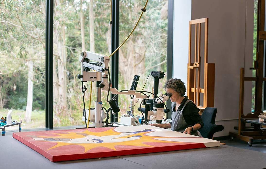 """Paintings conservator Tricia O'Regan examines Phillip Lindsay Mason's """"The Hero"""" in the paintings conservation studio at the de Young"""