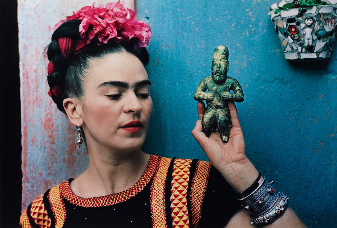 "Nickolas Muray, ""Frida with Olmeca Figurine, Coyoacán,"" 1939. Color carbon print, 10 3/4 x 15 3/4 in. (27.3 x 40 cm). Fine Arts Museums of San Francisco, Gift of George and Marie Hecksher in honor of the tenth anniversary of the new de Young museum. 2018.68.1. © Nickolas Muray Photo Archives"