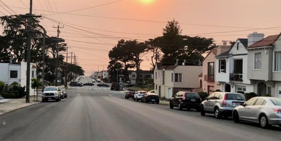 Photo of street lined with houses and cars at sundown