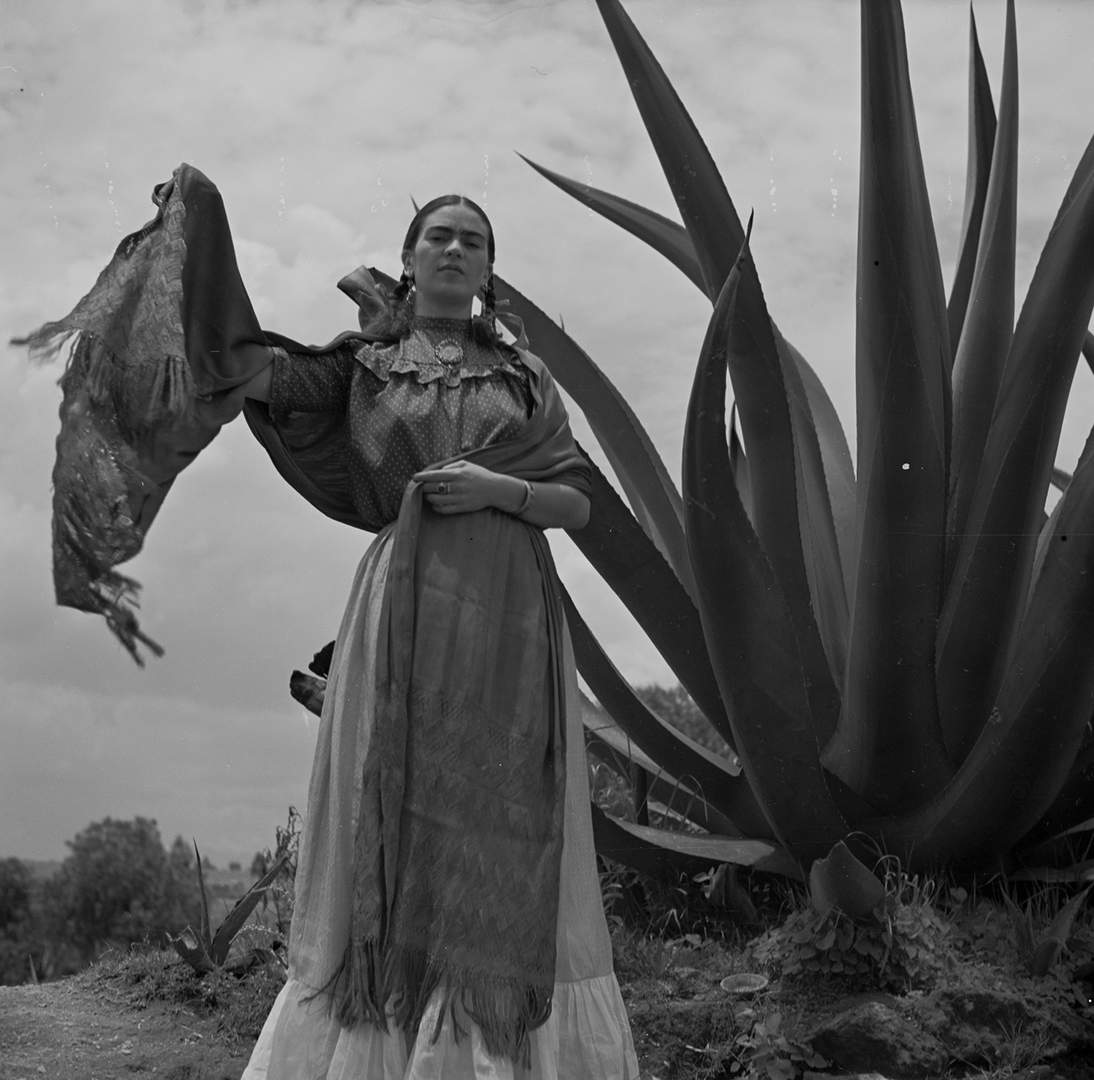 "Toni Frissell, Frida Kahlo (Senora Diego Rivera) standing next to an agave plant, during a photo shoot for Vogue magazine, ""Senoras of Mexico,"" 1937 Negative, nitrate. Library of Congress, Washington, D.C. Library of Congress, Prints & Photographs Division, Toni Frissell Collection, LC-DIG-ds-05052"