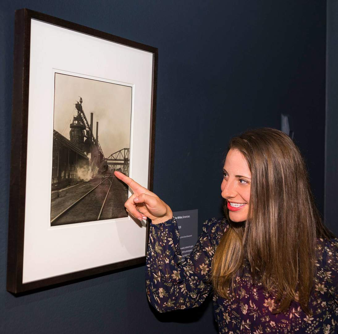 "Lauren Palmor, Assistant Curator of American Art, points out the two mill workers, small in scale, situated in the background of Margaret Bourke-White's ""Otis Steel Works"" (1928). Art © Estate of Margaret Bourke-White / Licensed by VAGA, New York, NY. Photo: Randy Dodson"