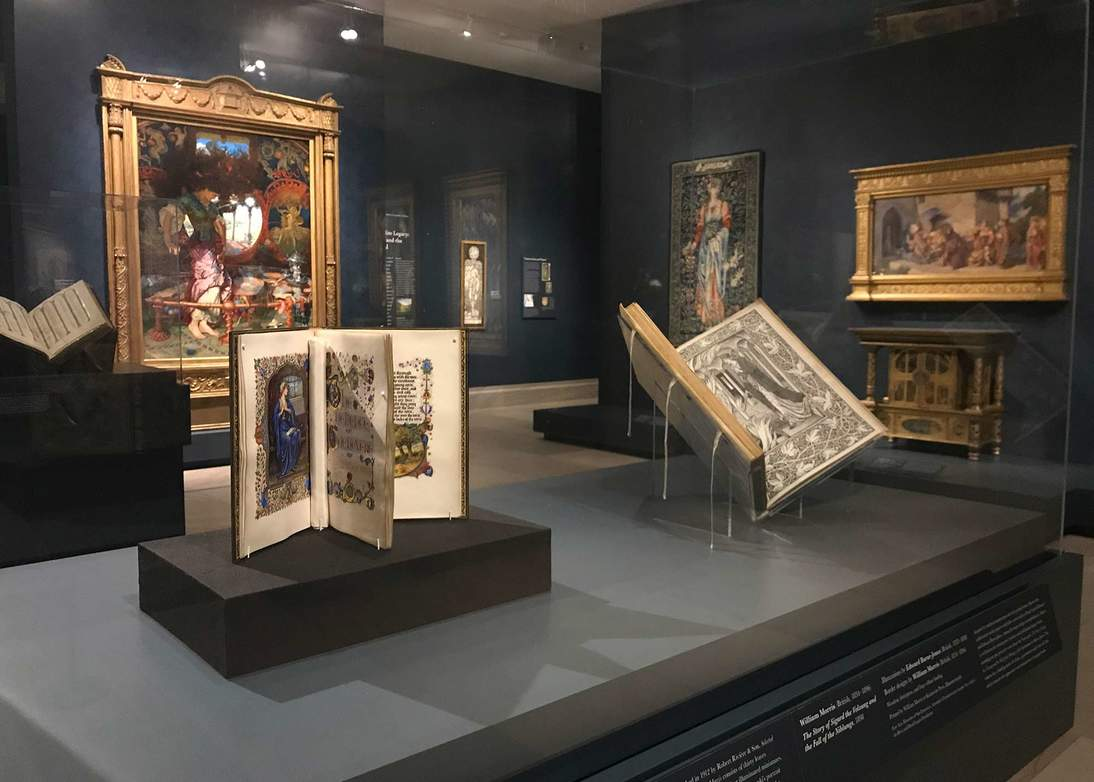 """Gallery view of """"Truth and Beauty"""" at the Legion of Honor. The case in the foreground houses """"The Selected Poems of William Morris"""" whose minimally-visible upright mounting system allows for more visibility than a traditional book cradle, seen supporting the other two books in the image."""