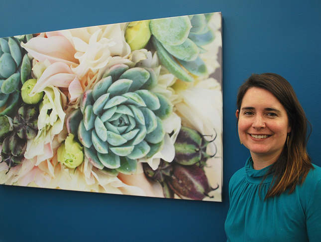 A brunette woman in a teal top stands in front of a picture of succulent plants