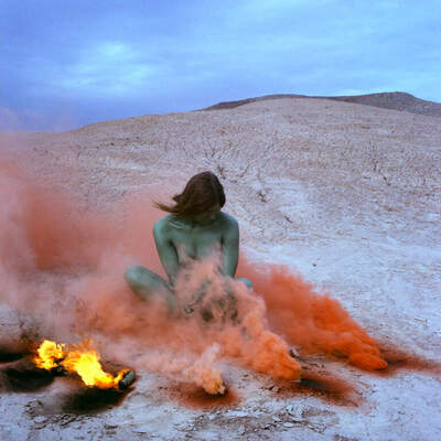 A woman in the desert next to a fire surrounded by pink smoke