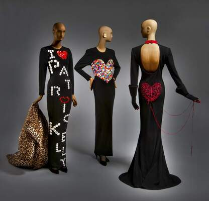 Image of three wooden mannequins wearing gowns designed by Patrick Kelly