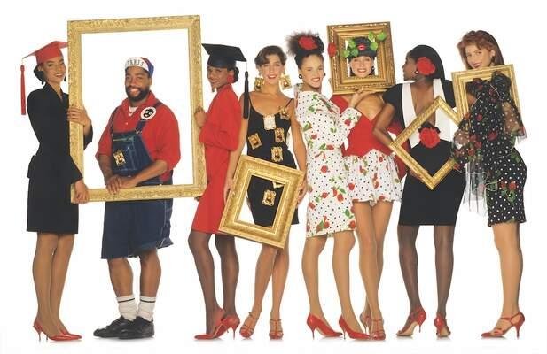 people wearing black, red, and white holding large picture frames