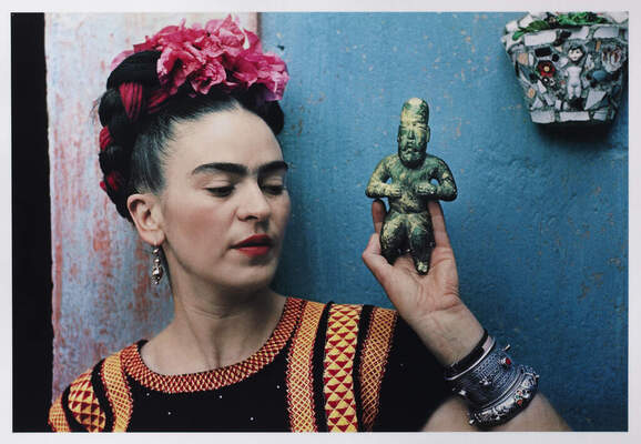 Photograph of a close shot of Frida Kahlo's head and shoulders in front of a bright blue wall. Her face is turned slightly to her left as she looks at a small figurine she is holding in her left hand up by her shoulder. She is wearing a bright pink flower on the top of her head and her hair appears to be swept up on the top of her head.