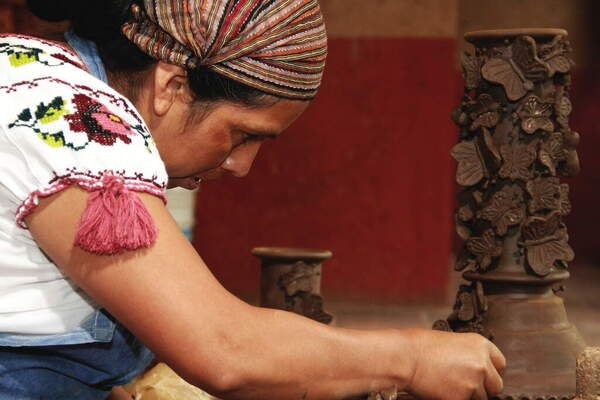 Image of a woman creating pottery butterflies .
