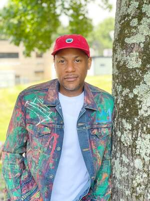 Man in paint decorated denim jacket and red hat posing against a tree .