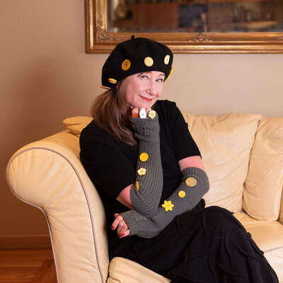 Woman wearing all black outfit with yellow buttons on it, sitting on a couch, smiling.