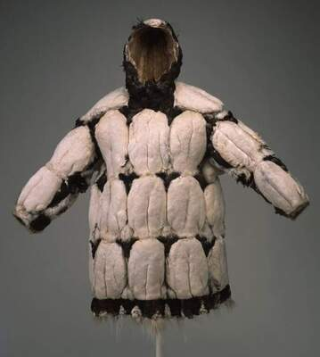 Image of a man's parka with hood that is covered with white feathers and stitched with dark brown and gray dog and wolf hair and plant fibers..