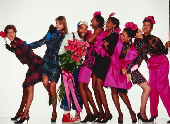 Patrick Kelly smiling, surrounded by models, also smiling, who are wearing bright pink clothing